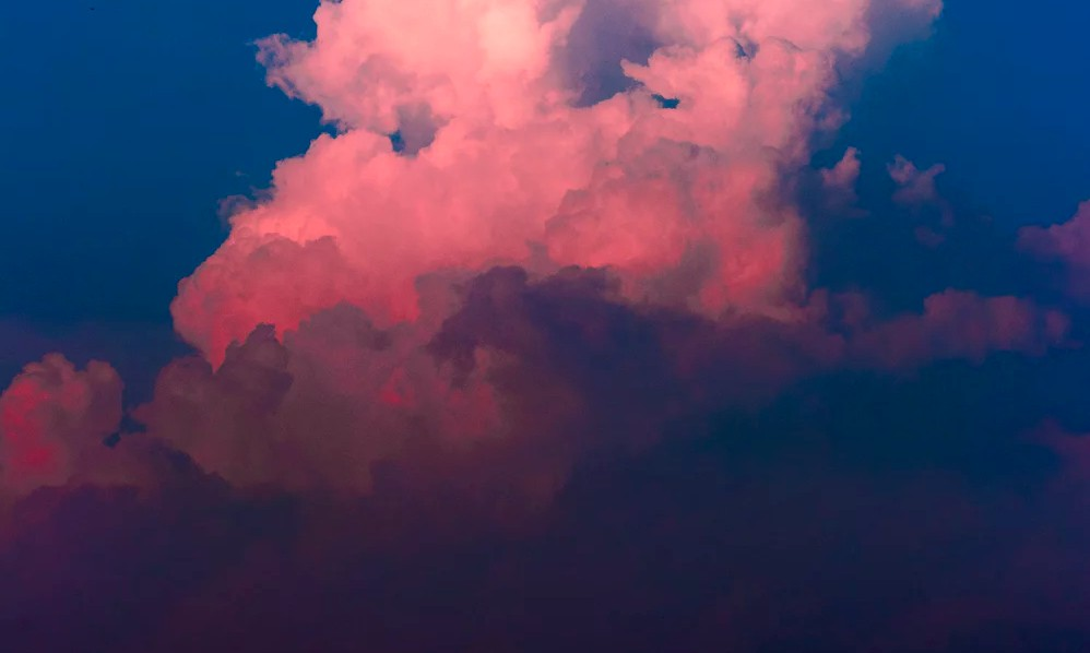 Pink hues of a cloud in blue sky