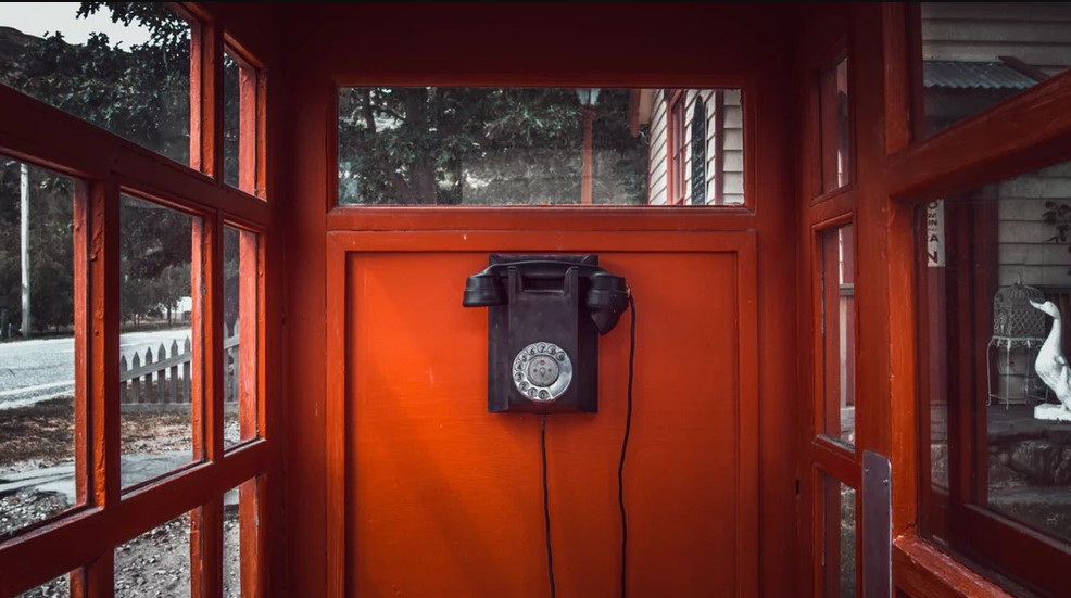 Discolored red phone booth with a black colored telephone