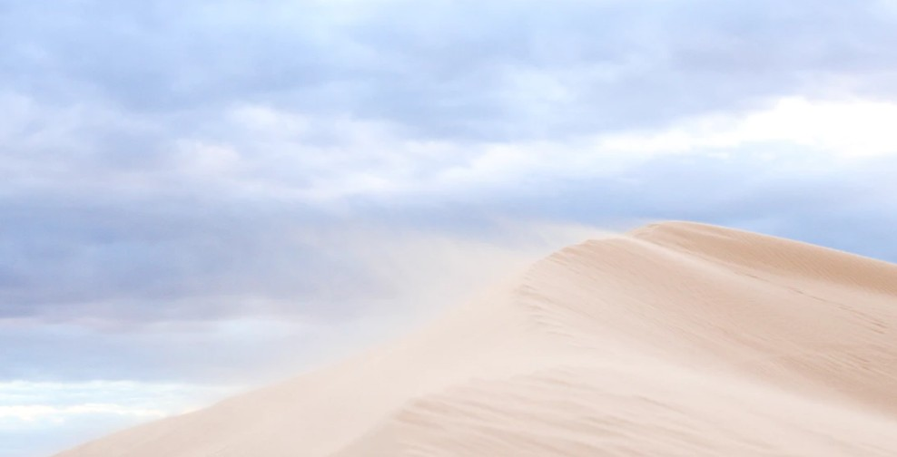 Desert under white and grey clouds