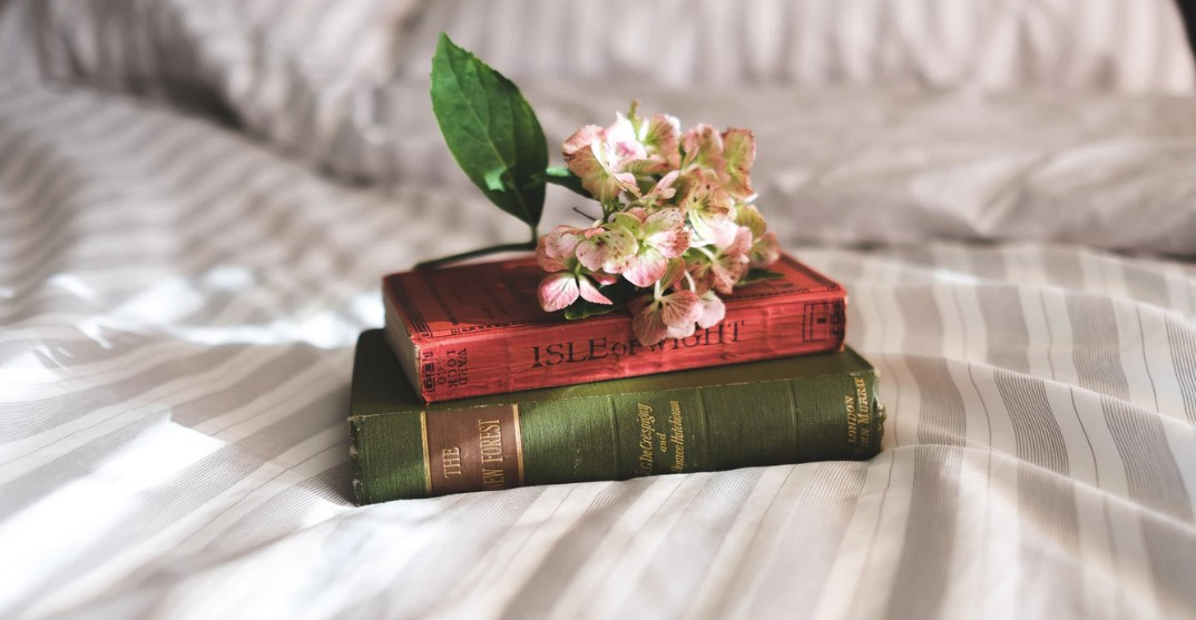 A couple of books and flowers on the bed