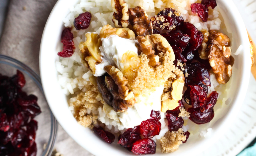 A bowl of yogurt with walnuts and cranberries