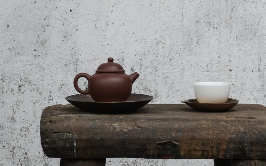 Teapot and tea cup on a wooden bench
