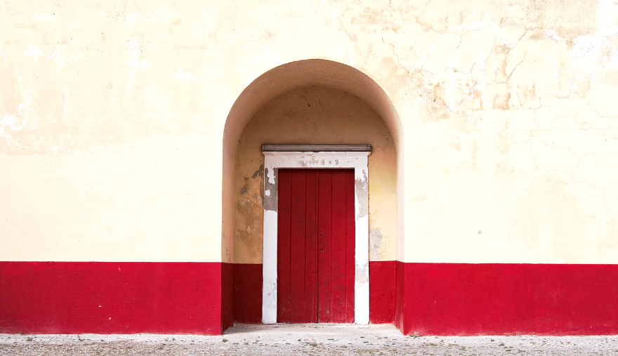 Red painted door with cream colored walls