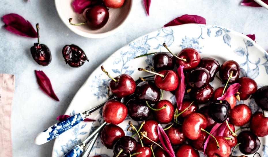 A plate of bright and dark red cherries